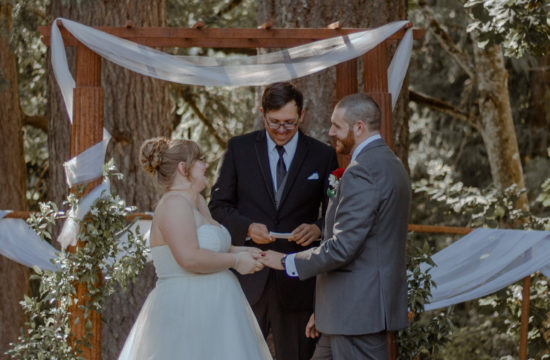 Bride and Groom hold hands at alter